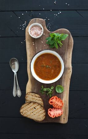 hot soup: Roasted tomato soup with fresh basil, spices and bread in vintage metal bowl on wooden board over black background, top view