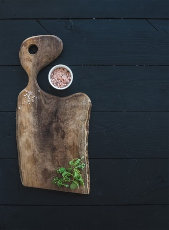boards: Kitchen-ware set. Old rustic chopping board made of walnut wood, salt and oregano herb on a black background, top view, copy space