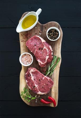 Raw fresh meat Ribeye steak entrecote and seasonings on cutting board on dark wooden background, top view 写真素材