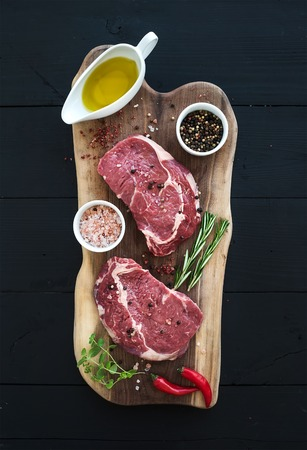 Raw fresh meat Ribeye steak entrecote and seasonings on cutting board on dark wooden background, top view Banco de Imagens
