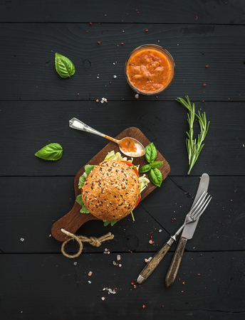 classic burger: Fresh homemade burger on dark serving board with spicy tomato sauce, sea salt and herbs over dark wooden background. Top view Stock Photo