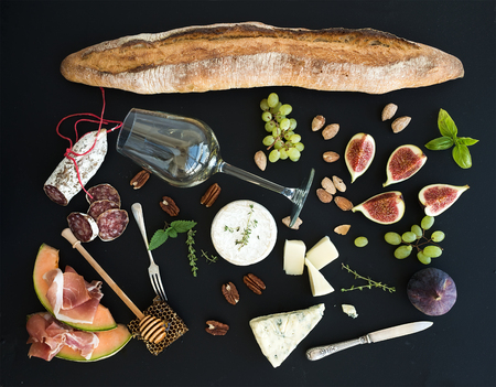 antipasto: Wine and snack set. Baguette, glass of white, figs, grapes, nuts, cheese variety, meat appetizers and herbs on black grunge background, top view