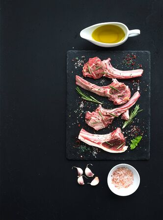 lamb shank: Raw lamb chops. Rack of Lamb with garlic, rosemary and spices on black slate tray, oil in a saucer, salt, dinnerware over dark rustic wood background, top view, copy space Stock Photo