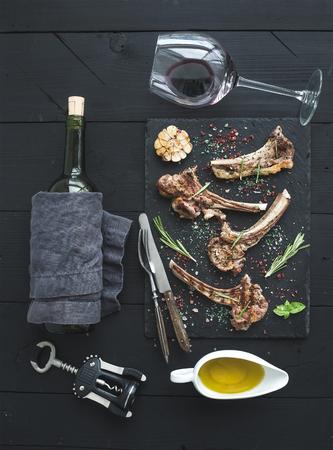 copa de vino: chuletas de cordero a la parrilla. Rack de cordero con ajo, romero y especias en la bandeja de pizarra, copa de vino, el aceite en un platillo, atornillador corcho y la botella sobre fondo negro de madera. Vista superior