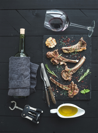 Grilled lamb chops. Rack of Lamb with garlic, rosemary and spices on slate tray, wine glass, oil in a saucer, cork screwer and bottle over black wood background. Top view Stock Photo