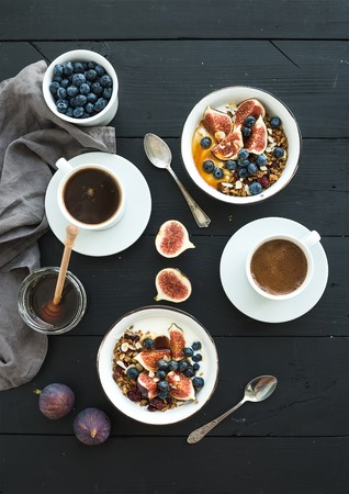 Healthy breakfast set. Bowls of oat granola with yogurt, fresh blueberries and figs, coffee, honey, over black wooden backdrop. Top view