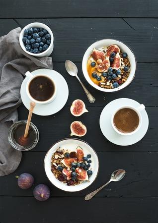 건강 한 아침 식사 세트입니다. 검은 나무 배경 위에 요구르트, 신선한 블루 베리와 무화과, 커피, 꿀, 귀리 놀라의 그릇. 평면도