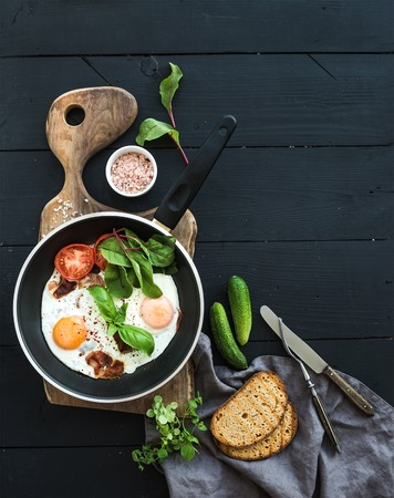 Pan of fried eggs, bacon, tomatoes with bread, mangold and cucumbers on rustic wooden serving board over dark table surface, top view, copy space