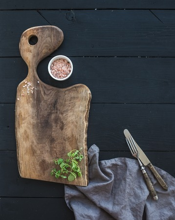 ustensiles de cuisine: Kitchen-ware set. Old rustic chopping board made of walnut wood, salt and oregano herb on a black background, top view, copy space