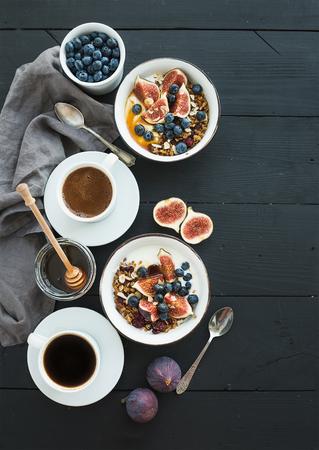 Gezond ontbijt. Kommen van havergranola met yoghurt, verse bosbessen en vijgen, koffie, honing, over zwarte houten achtergrond. Bovenaanzicht, kopie ruimte