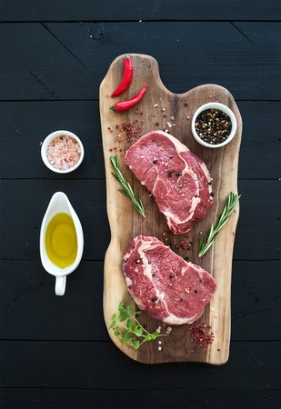 Raw fresh meat Ribeye steak entrecote and seasonings on cutting board on dark wooden background, top view Stok Fotoğraf