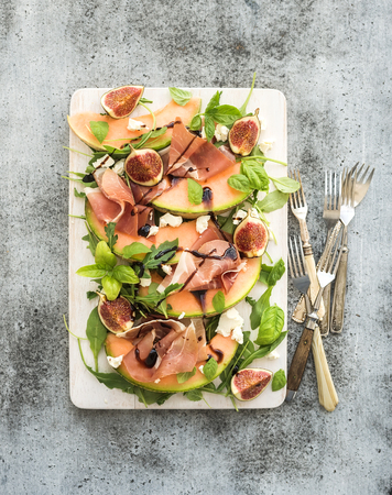 salad dressing: Prosciutto, melon, fig and soft cheese salad on a white serving board over grunge background, top view