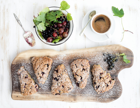 cup cakes: Fresh black-currant scones with coffee and bowl of berries over rustic walnut wood serving board, top view, copy space