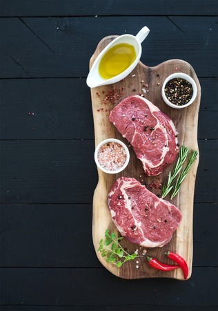 Raw fresh meat Ribeye steak entrecote and seasonings on cutting board on dark wooden background, top view, copy space