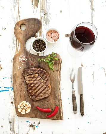 steak plate: Grilled ribeye beef steak with herbs, spices  and glass of red wine on walnut cutting board over white rustic wooden background, top view