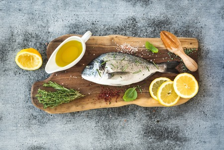 fish: Fresh uncooked dorado or sea bream fish with lemon, herbs, oil and spices on rustic wooden board over grunge backdrop, top view