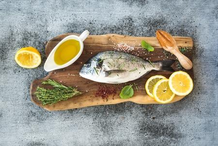 Verse ongekookte dorado of zeebrasem vissen met citroen, kruiden, olie en kruiden op rustieke houten bord op grunge achtergrond, bovenaanzicht