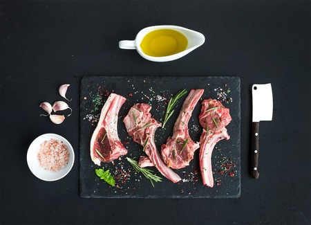 Raw lamb chops. Rack of Lamb with garlic, rosemary and spices on black slate tray, oil in a saucer, salt, dinnerware over dark rustic wood background