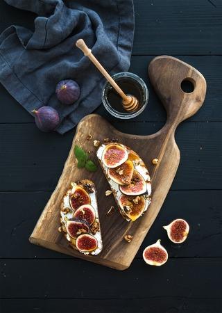 comiendo pan: S�ndwiches con queso ricotta, higos frescos, nueces y miel en tabla de madera r�stica sobre fondo negro, vista desde arriba