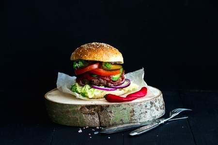 Fresh homemade burger on wooden serving board with spicy tomato sauce, sea salt and herbs over black  background Standard-Bild