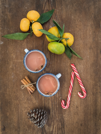 hot drinks: Christmas or New Year attributes. Fresh mandarins with leaves, cinnamon sticks, pine cone, hot chocolate in mugs and candy canes over rustic wooden background, top view