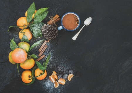hot chocolate: Navidad o año nuevo marco. mandarinas frescas con hojas, ramas de canela, vainilla, piña de pino y una taza de chocolate caliente sobre el fondo de piedra oscura, vista desde arriba, espacio de copia