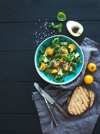 Bowl of green salad with avocado, arugula, cherry tomatoes and sunflower seeds, grilled bred slices, fresh herbs over black wooden backdrop, top view
