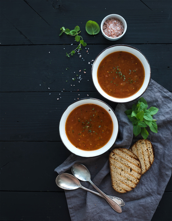 black bread: Roasted tomato soup with fresh basil, spices and bread in rustic metal bowls over black background, top view, copy space Stock Photo