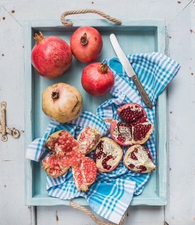 tropical food: Red and white pomegranates and knife on kitchen towel in blue tray over light painted wooden backdrop, top view