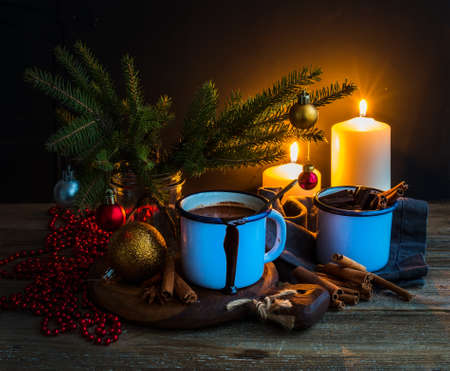 fur tree: Christmas food and decorations set. Fur tree branches, mug of hot chocolate, colorful glass balls, burning candles and cinnamon sticks, dark background, selective focus