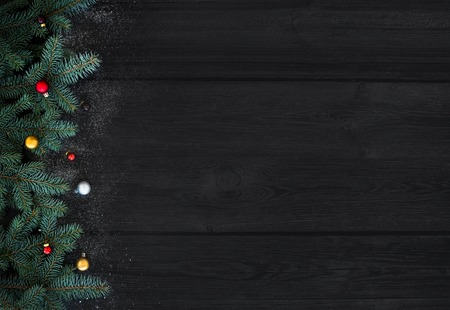 Christmas or New Year decoration background: fur-tree branches, colorful glass balls on black wood background with copy space