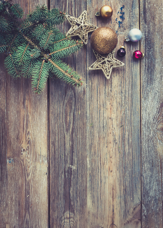 christmas backdrop: Christmas or New Year rustic wooden background with toy decorations, candy cane and fur tree branch, top view, copy space