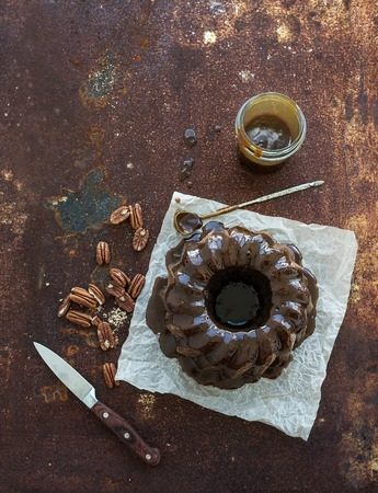 rusty: Chocolate coffee bundt cake with salt caramel icing over grunge rusty metal backdrop, top view, selective focus, copy space Stock Photo