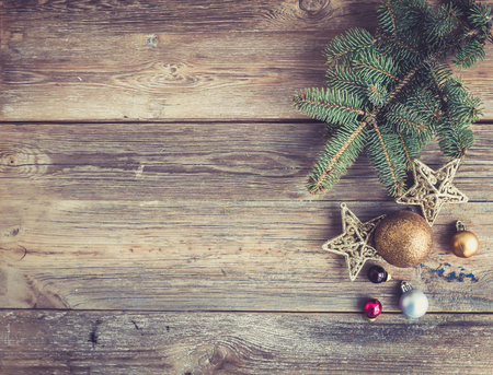 top of the year: Christmas or New Year rustic wooden background with toy decorations and fur tree branch, top view, copy space