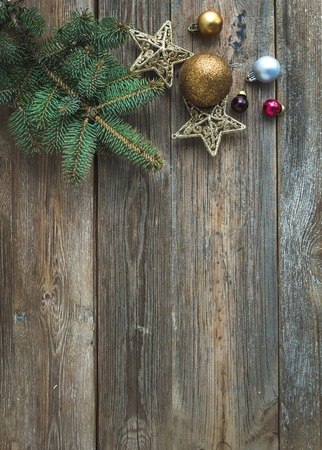 fur tree: Christmas or New Year rustic wooden background with toy decorations, candy cane and fur tree branch, top view, copy space