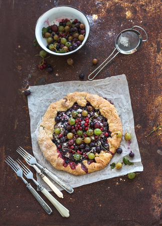 Summer crostata or galette pie with fresh garden berries and vanilla ice-cream over grunge rusty metal background, top view