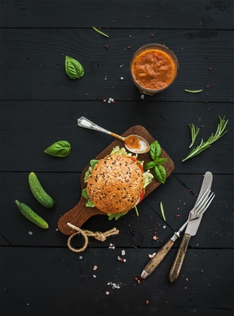 rustic food: Fresh homemade burger on dark serving board with spicy tomato sauce, sea salt and herbs over dark wooden background. Top view Stock Photo