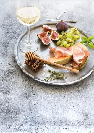 pan y vino: establece aperitivo vino. Vaso de vino blanco, panal con drizzlier, higos, melón con jamón y las uvas en la bandeja de plata sobre la superficie del grunge rústico. Foto de archivo
