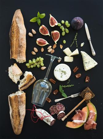 ワインし、軽食のセット。バゲット、ホワイト、イチジク、ブドウ、ナッツ、チーズ各種、肉料理の盛り合わせ、黒グランジ背景、上面にハーブの 写真素材