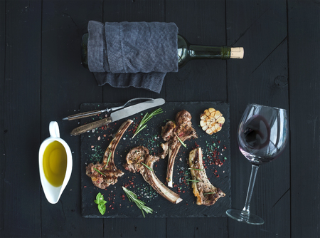 Grilled lamb chops. Rack of Lamb with garlic, rosemary and spices on slate tray, wine glass, oil in a saucer and bottle over black wood background. Top view Banco de Imagens
