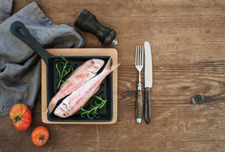 goatfish: Raw uncooked Red Mullet fish in a cooking pan with rosemary, lemon and garlic over rustic wooden background, top view, copy space Stock Photo