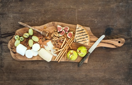 Wine appetizers set: cheese selection, honey, grapes, almonds, walnuts, bread sticks, figs on olive wood serving board over rustic background , top view Stock Photo
