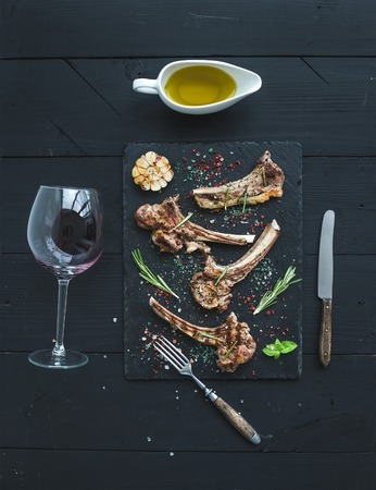 lamb shank: Grilled lamb chops. Rack of Lamb with garlic, rosemary and spices on slate tray, wine glass, oil in a saucer over black wood background. Top view