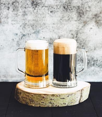 still life: Light and dark beer in mugs on wooden board, grunge backdrop