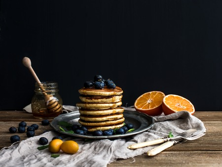 breakfast plate: Pancake tower with fresh blueberries, oranges and mint on a rustic metal plate, dark background