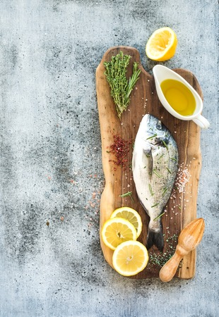 sea bream: Fresh uncooked dorado or sea bream fish with lemon, herbs, oil and spices on rustic wooden board over grunge backdrop, top view, copy space