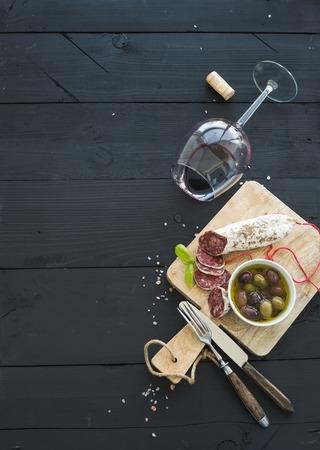 Wijn voorgerecht te stellen. Glas rode wijn, Franse worst en olijven op zwarte houten achtergrond, bovenaanzicht, kopieer ruimte
