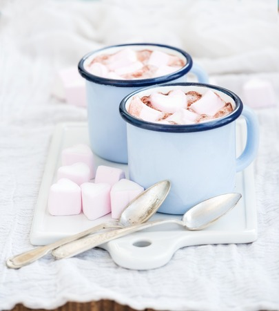 Seint Valentine's holiday greeting set. Hot chocolate and heart shaped marshmallows in old enamel mugs on white ceramic serving board, selective focus 스톡 콘텐츠