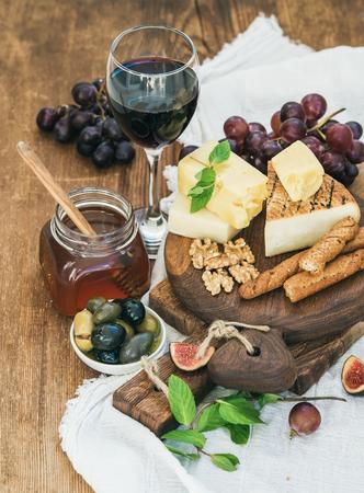 pan y vino: Vaso de vino tinto, tabla de quesos, uvas, higos, fresas, miel y palitos de pan en la mesa de madera rústica, enfoque selectivo