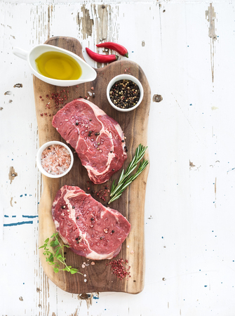 Raw fresh meat Ribeye steak entrecote and seasonings on cutting board over white wooden background, top view, copy space Banque d'images
